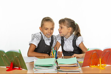 two girls whisper while sitting at