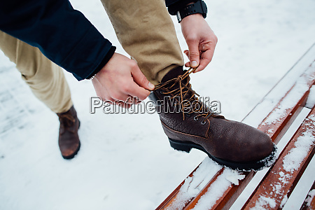 shoelaces of boots man tying shoelaces