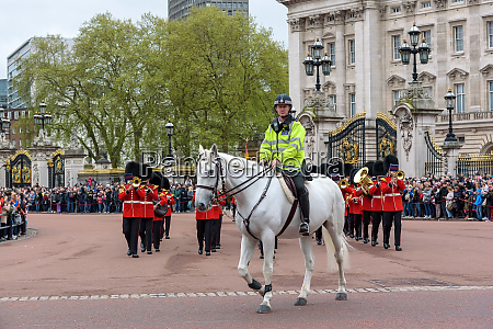 mounted police officer leads marching royal