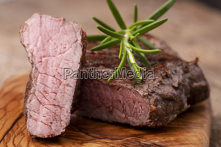 grilled steak on wood with rosemary