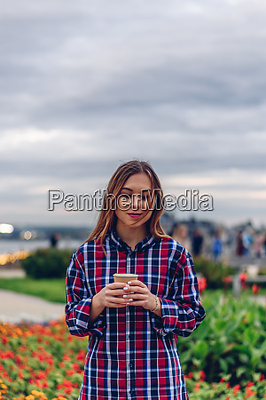 beautiful young woman holding coffee cup