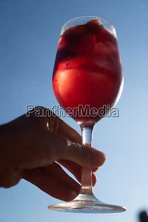 hand serving sangria with red wine