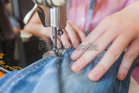 woman tailor using retro sewing machine