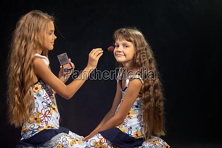 the older sister is applying powder