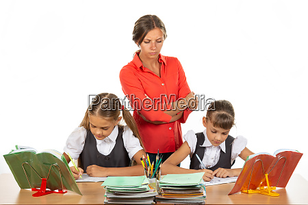 a strict teacher stands above the
