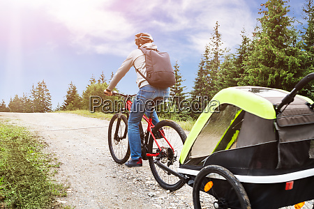 father with child in trailer riding