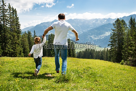 father and daughter running on field