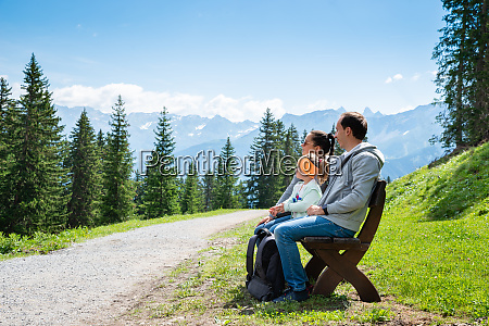 family sitting on bench in mountains