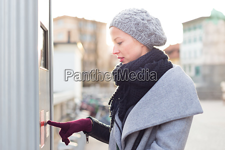 casual woman buying public transport tickets