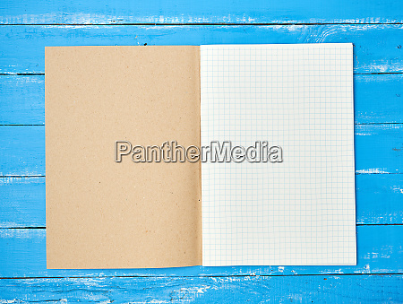 open checked school notebook on blue