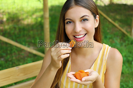 young woman eating dried fruits in