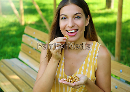 brazilian woman eating walnuts in the