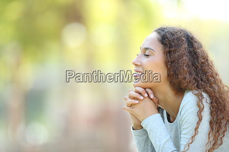 happy mixed race woman meditating outdoors
