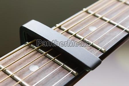 black capo on acoustic guitar string
