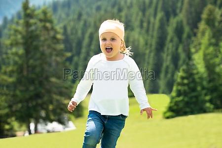 happy girl running on green meadow