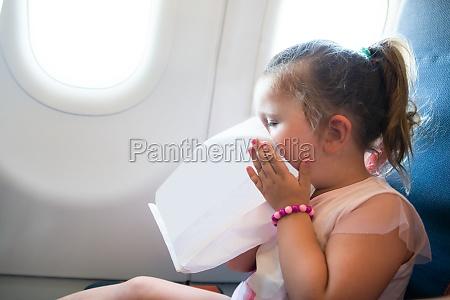 little girl sitting on flight vomiting