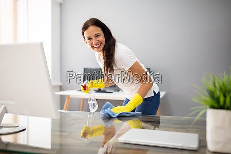 janitor cleaning desk with napkin