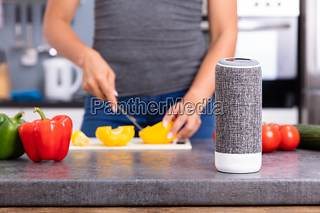 woman listening music on smart speaker