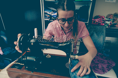 woman tailor using retro sewing machine