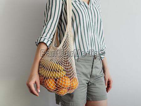 woman standing with mesh bag on