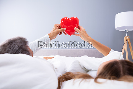 couple holding red heart in hands