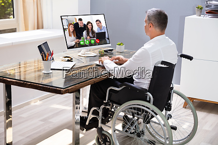 businessman sitting on wheelchair and using
