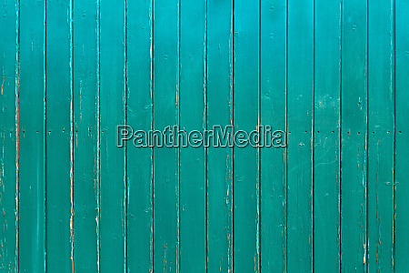 slightly weathered turquoise wooden wall of