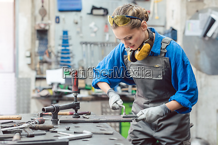 woman mechanic working in metal workshop