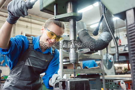 woman worker in metal workshop using