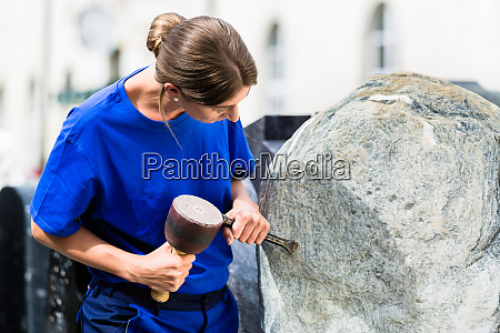 stonemason working on boulder with sledgehammer