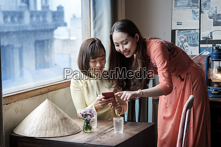 two friends in ao dai dresses