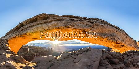 the sun rising under mesa arch
