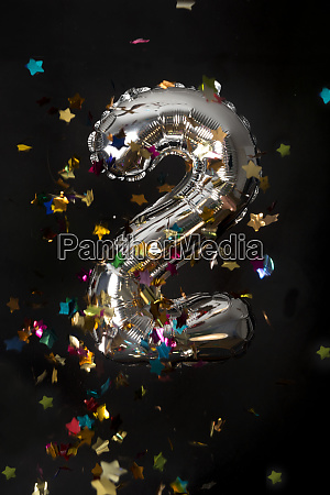 silver balloon and confetti for second