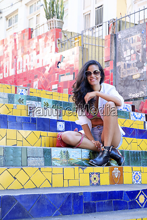 young brazilian woman in sunglasses sitting