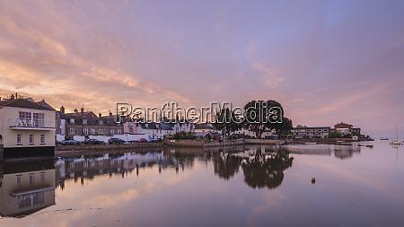 soft dawn sky over riverside properties
