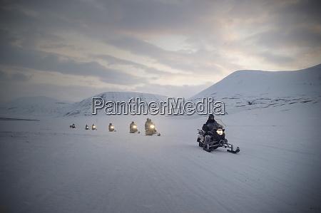 tourists on snowmobiles skidoos near barentsburg