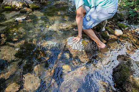 man crossing the stream barefoot