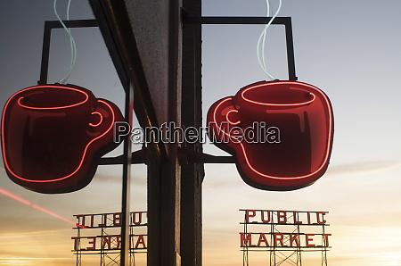 neon coffee mug reflected in coffee