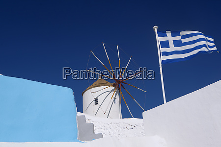 church windmill and greek flag santorini