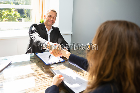 smiling mature businessman shaking hand with