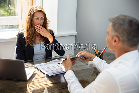 woman looking at report holding by