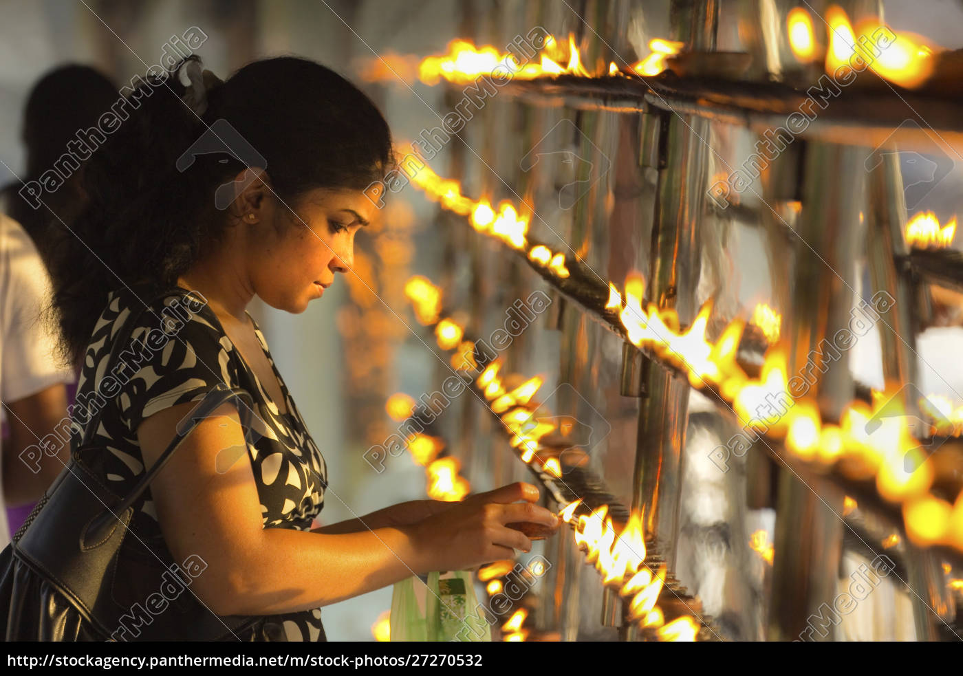 devotee, lighting, candles, at, sunset, in - 27270532