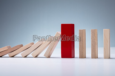 red wooden block amidst falling and