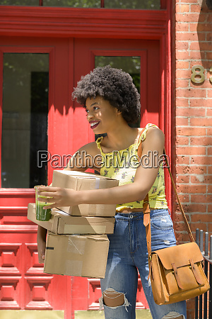 woman carrying cardboard boxes and green