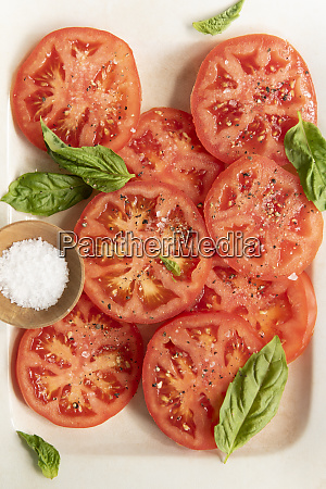sliced tomatoes with basil and salt