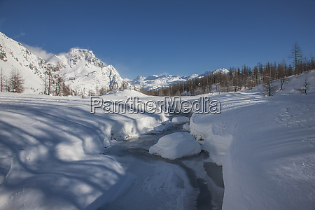 frozen river in snow covered mountainous