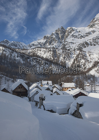 snow covered village by mountain in