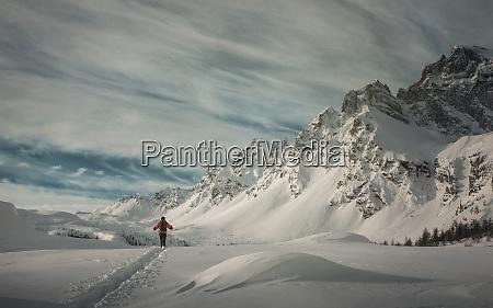 man hiking through snow by mountain