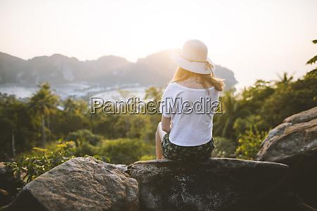 woman wearing straw hat sitting on