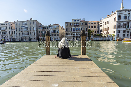 woman sitting on jetty on grand